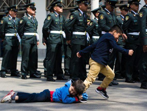 Niños juegan cerca de un grupo de militares. (Foto: Tito Mariátegui)